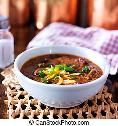 bowl of chili with scallions and grated cheese