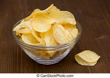 Bowl of chips on wooden table close up view