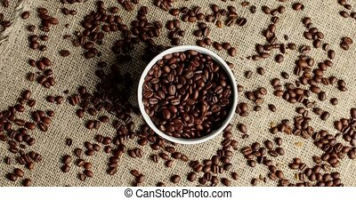 Bowl of coffee beans on canvas - Top view of white round...