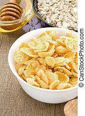 bowl of corn and oat on wood background