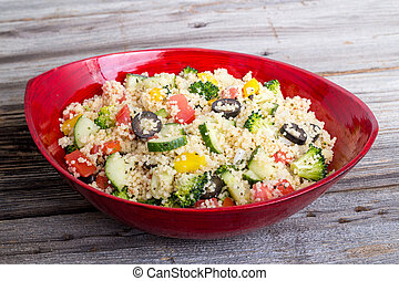 bowl of couscous salad with cucumber, pepper, tomato and...