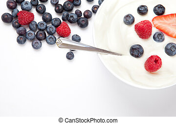 Bowl of cream with berries and a spoon