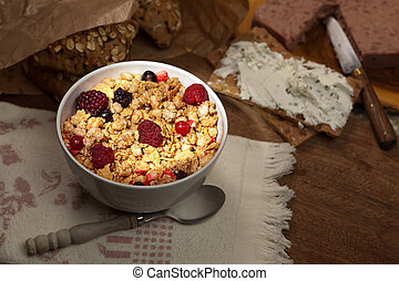 Bowl of crunchy cereals with fresh red fruit highlited on a...