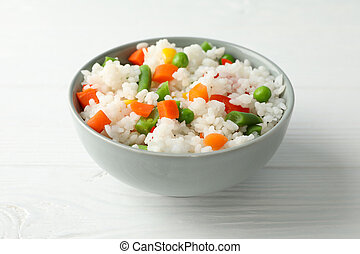 Bowl of delicious rice with vegetables on wooden background, close up