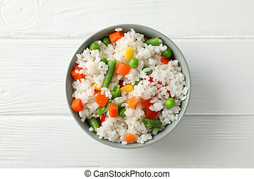 Bowl of delicious rice with vegetables on wooden background, top view