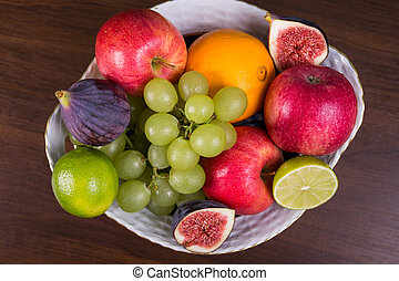 Bowl of different fruits on wooden table