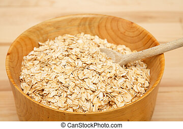 Bowl of Dry Oats with Wood Spoon