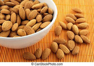 Bowl of almonds on rattan mat of warm orange color.