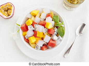 Bowl of fresh exotic fruit salad on white summer background Healthy breakfast Top view