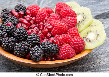 Bowl of fresh exotic tropical fruit with colourful neat rows of blackberries, pomegranate seeds, raspberries and thinly sliced kiwifruit on a stone counter for a delicious healthy vegetarian dessert