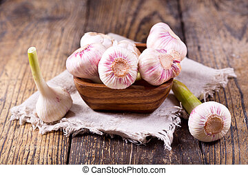 fresh garlic on a wooden table - bowl of fresh garlic on a ...
