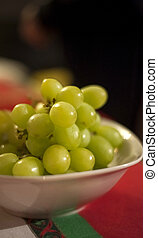 Bowl of fresh green grapes on colorful Christmas tablecloth