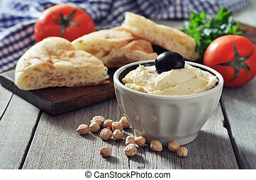 Bowl of fresh hummus with olive and bread slices on wooden ...