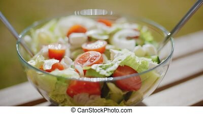 Bowl of fresh mixed green salad with lettuce leafy greens...