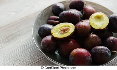 Bowl of fresh plums in daylight - From above shot of ...