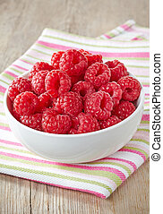 Bowl of fresh raspberries on striped tablecloth