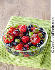 Bowl of fresh ripe berries on green tablecloth