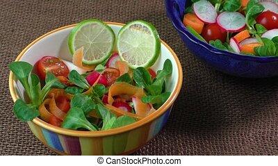 Bowl of fresh vegetable salad on jute table cloth