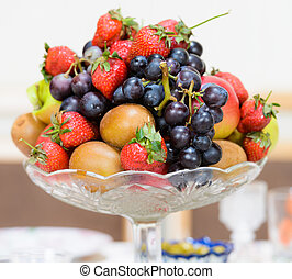grape apple kiwi strawberry lie in a vase close up