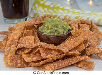 Bowl of Guacamole and Chips with Drink and Napkin in Background