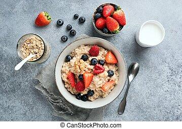 Bowl of healthy breakfast oatmeal porridge bowl served with summer berries
