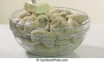 Bowl of homemade boiled dumplings with butter. Traditional Russian dish pelmeni
