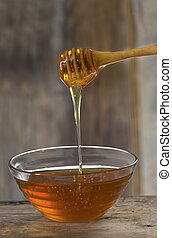 Bowl of honey and a dipstick - Honey pouring from drizzler...