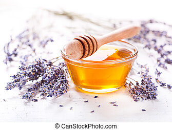 bowl of honey and lavender flowers on wooden table