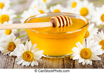 bowl of honey with daisy flowers on wooden table