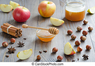 Bowl of honey with honey stick, cinnamon, hazelnuts, apples and spices