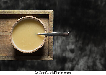 bowl of hot soup on a wooden tray