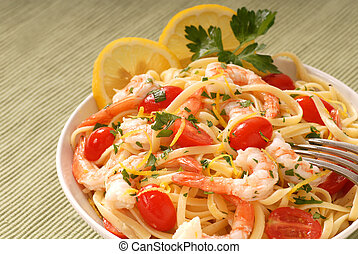 Bowl of lemon pasta with shrimp and tomatoes - A bowl of...