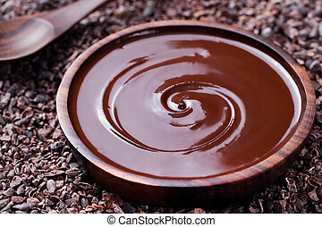Bowl of melted chocolate and wooden spoon on a crushed raw...