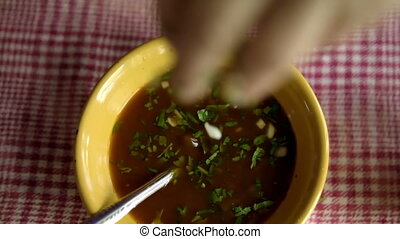 Top view of hand slowly adding chopped coriander and onion to yellow bowl of tasty beef stew. Authentic delicious meat broth above white and red checkered tablecloth. Traditional Mexican cuisine