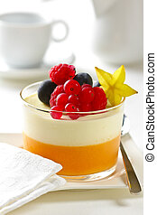 Bowl of mixed berries and yogurt with blueberries, raspberries and cranberries served on a white table