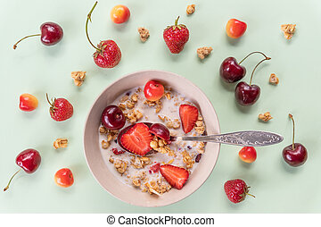 bowl of muesli and yogurt with fresh cherries, strawberries.diet breakfast - bowls of oat flake, berries and fresh milk on green background. health and diet concept