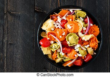 Bowl of multicolored tortellini pasta salad with tomatoes and onions, overhead view on a dark wood background