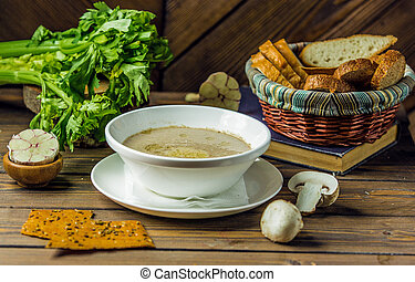 bowl of mushroom soup served with garlic and cracker