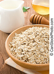 Bowl of oat and milk on wood background