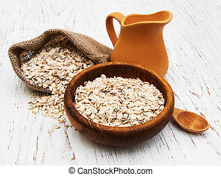 bowl of oat flake and milk on a wooden background