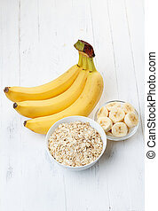 Bowl of oat flakes with sliced banana on wooden table
