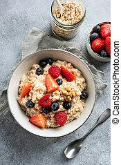 Bowl of oatmeal porridge with fresh berries top view