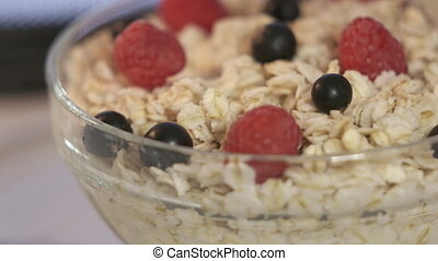 Bowl of oatmeal with fresh berries rotating inside microwave