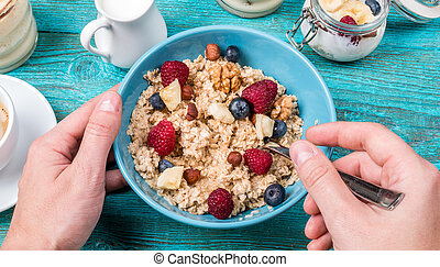 Bowl of oatmeal with raspberries and blueberries on a blue wooden table.