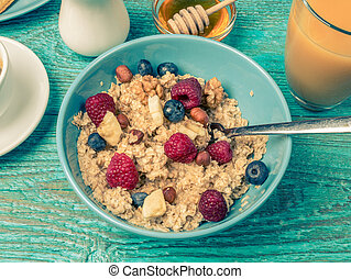 Bowl of oatmeal with raspberries and blueberries on a blue wooden table. Toned photo.