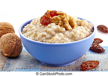 Bowl of oats porridge with raisins and nuts. Healthy ...