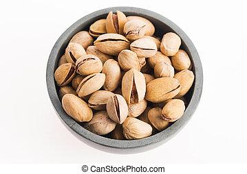 bowl of pistachios on white background