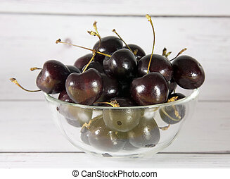 Bowl of ripe cherries on a wooden light background