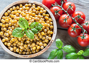 Bowl of roasted chickpeas on the wooden background - Bowl of...