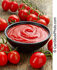 Bowl of tomato sauce or ketchup on old wooden table